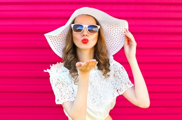 Woman-in-summer-straw-hat-sends-air-kiss-over-pink